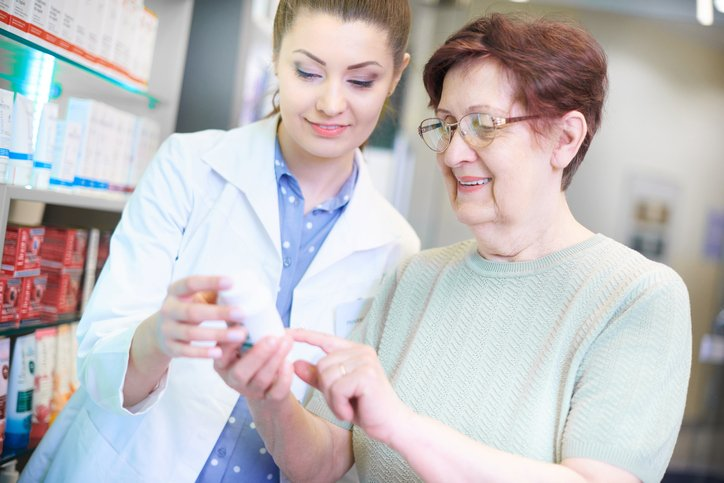 Pharmacist advising senior adult woman